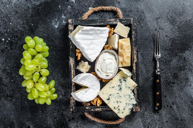 브리, 카망베르, 로크 포르, 파마산 치즈, 블루 크림 치즈, 포도, 견과류가 들어간 모듬 치즈 플래터. 검정색 배경. 평면도.