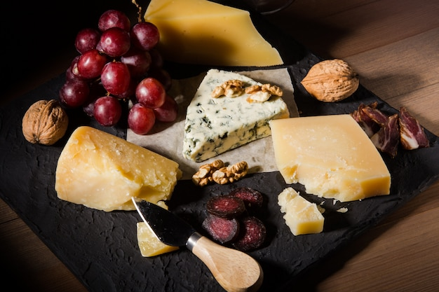 Assorted cheeses, nuts, grapes, fruits, smoked meat and a glass of wine on a serving table. dark and moody style. free space for text.