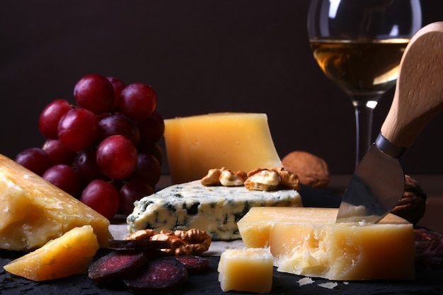 Assorted cheeses, nuts, grapes, fruits, smoked meat and a glass of wine on a serving table.