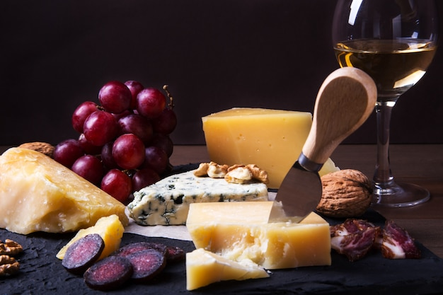 Assorted cheeses, nuts, grapes, fruits, smoked meat and a glass of wine on a serving table