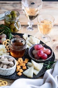 Ассорти сыров на темной тарелке на деревянном столе. сыр, виноград, грецкие орехи, оливки, розмарин и стакан белого вина.