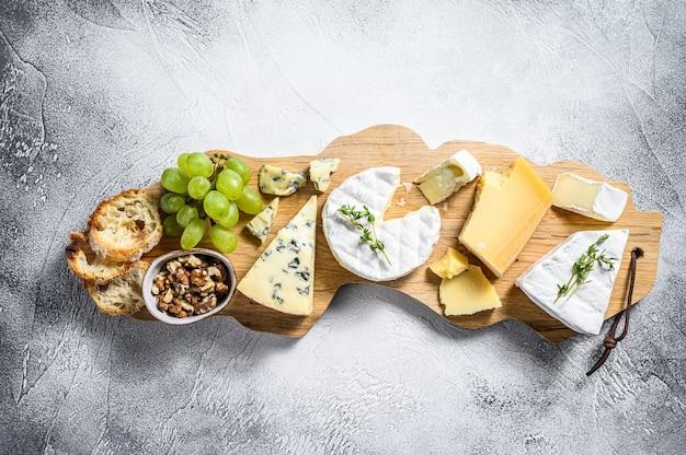 Ассорти сыров на деревянной разделочной доске. камамбер, бри, пармезан и голубой сыр с виноградом и грецкими орехами. белый фон. вид сверху