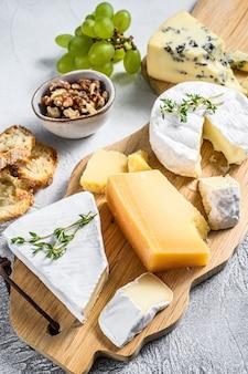 Ассорти сыров на деревянной разделочной доске.