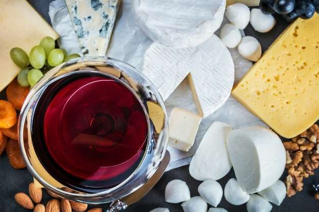 Assorted cheeses, soft, hard, rennet and brine, and a glass of red wine