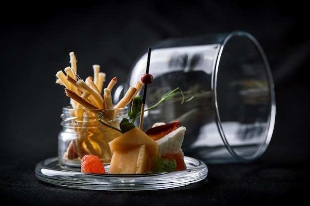 Assorted cheeses with berries and marmalade, mini serve in a glass flask. fusion food concept, low key, copy space.