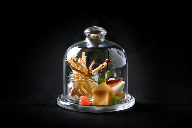 Assorted cheeses with berries and marmalade, mini serve in a glass flask.