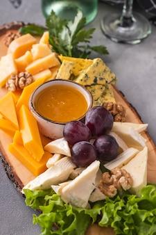 Ассорти сыров с медом, грецкими орехами и виноградом. вкусная сырная тарелка на деревянной доске. крупным планом