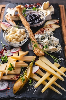 Assorted cheeses  with jam and pear on a black stone.