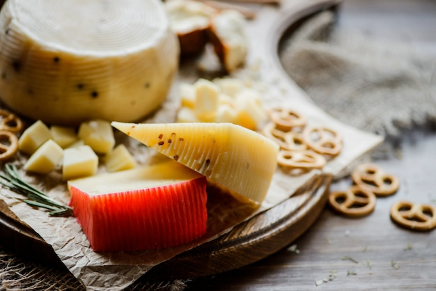 Ассорти сыров с кренделями на разделочной доске. на деревянном фоне выборочный фокус