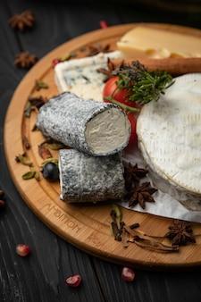 Ассорти сыров со специями и ягодами на деревянной доске