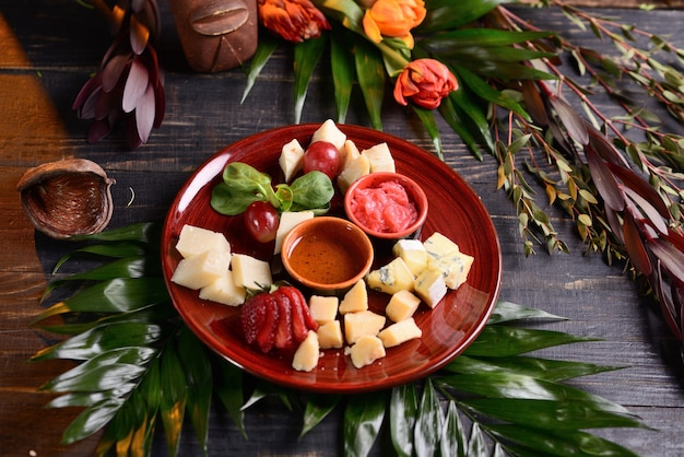 Assorted cheeses with strawberries, grapes and sauce. in a red plate. with flower decor