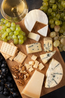 Assorted cheeses with white grapes.