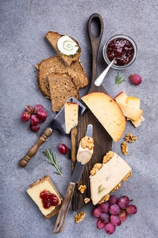 Assorted cheeses on wooden board plate, walnuts, grapes, bread on gray stone background