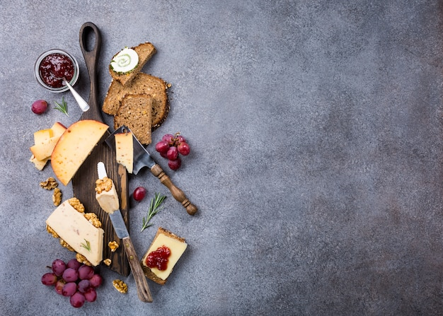 Assorted cheeses on wooden board