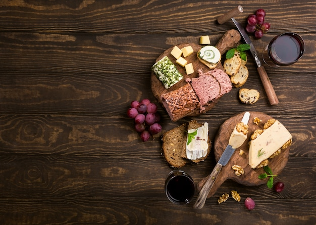 Assorted cheeses on wooden boards plate, grapes, bread wine and pate