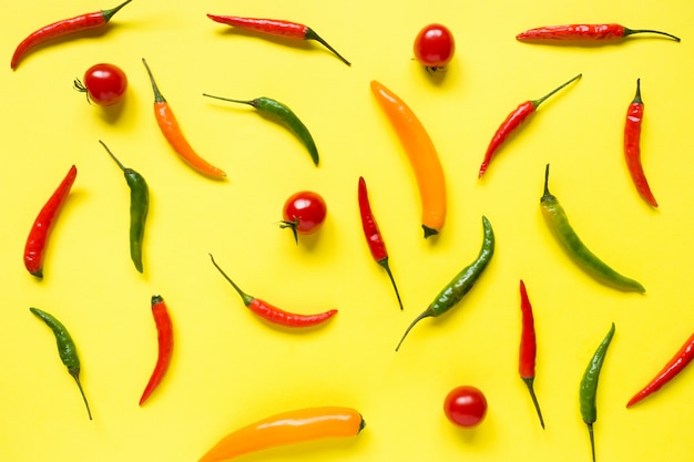 Assorted chili pepper tomato cherry on yellow bright background