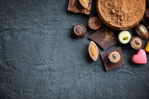 Assorted chocolate and cocoa powder on black