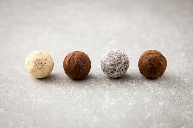 Assorted chocolate truffles with cocoa powder, coconut and chopped hazelnuts on a dessert plate