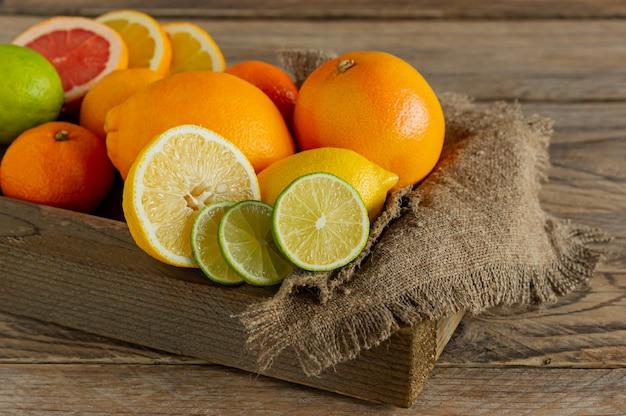 나무 상자에 모듬된 감귤류 과일입니다. 오렌지, 귤, 자몽, 레몬, 라임. 나무 배경에.