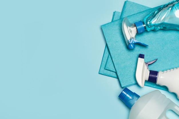 Бутылки ассорти чистящих средств на голубом фоне