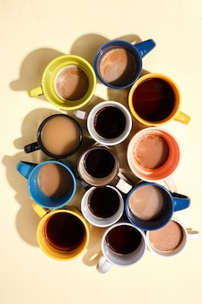 Assorted coffee cups with coffee and on a table. top view.