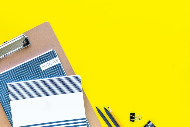 Assorted colorful stationery for school and office on yellow background with copyspace.