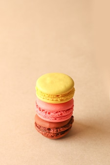 Assorted colorful sweet macaroons cookies on beige background