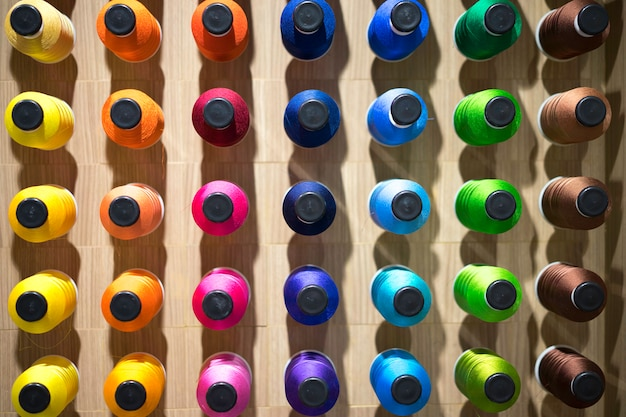 Assorted colors of thread on reels. embroidery process in the factory.