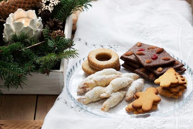 明るい背景に各種クッキー、モミの枝、花輪。素朴なスタイル、セレクティブフォーカス。