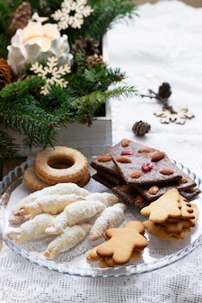 Assorted cookies, fir branches and a garland on a light background.