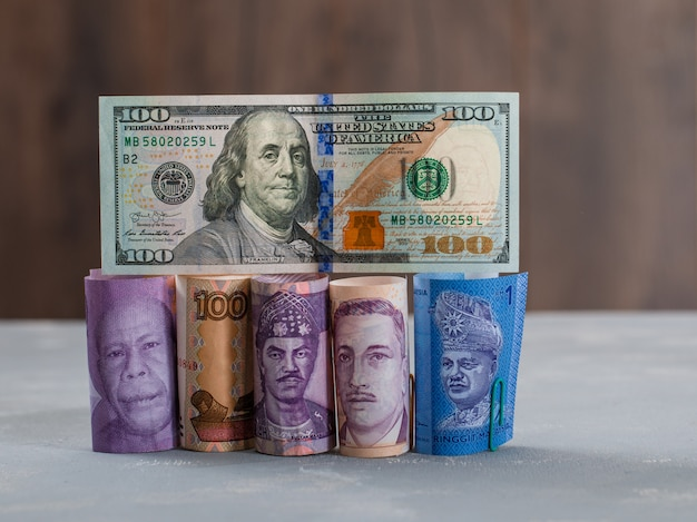 Assorted currency bills on plaster and wooden table .