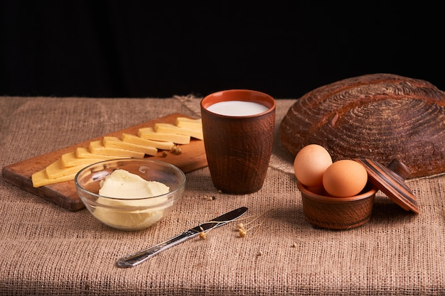 Assorted dairy products milk, cheese, butter rustic still life on table