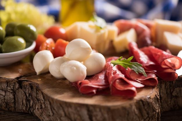 Мясное ассорти и тарелка сыра на деревянной разделочной доске. итальянские закуски