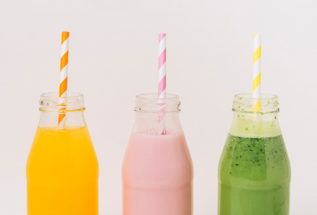 Assorted delicious fruit smoothies in bottles with straws