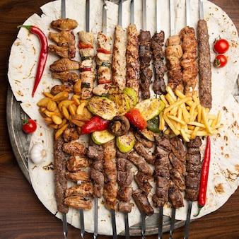 꼬치에 야채와 감자 튀김을 얹은 피타에 모듬 맛있는 구운 고기. 평면도