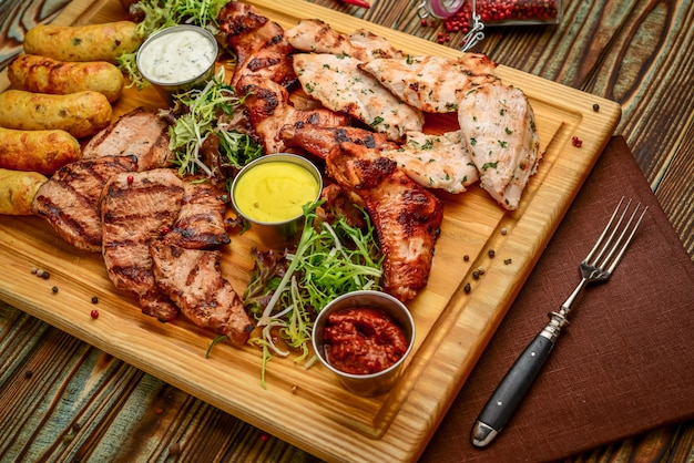 Assorted delicious grilled meat and vegetables with fresh salad and bbq sauce on cutting board on wooden background. big set of hot meat dishes
