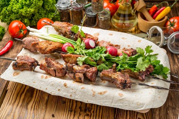家族のバーベキューパーティーのための白いプレートピクニックテーブルに野菜とおいしい焼き肉盛り合わせ