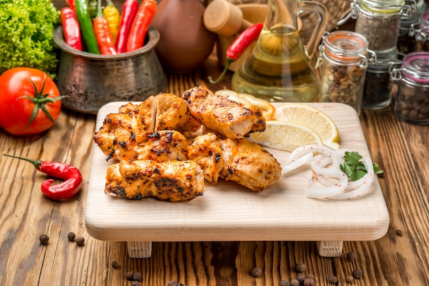 Assorted delicious grilled meat with vegetable on white plate  picnic table for family bbq party