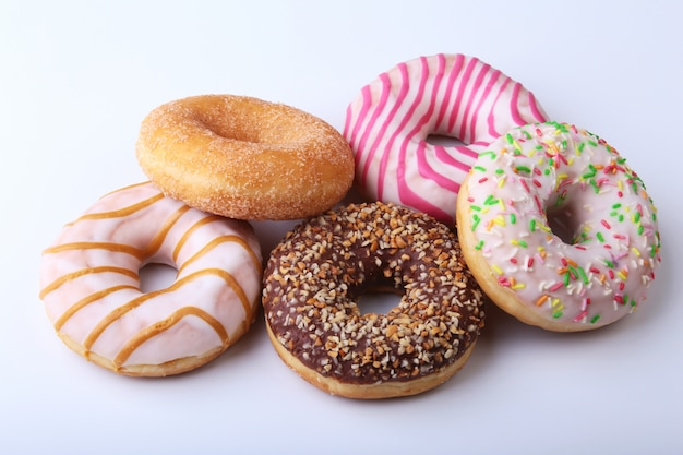 Assorted delicious homemade doughnuts in the glaze, colorful sprinkles and nuts isolated on white background.