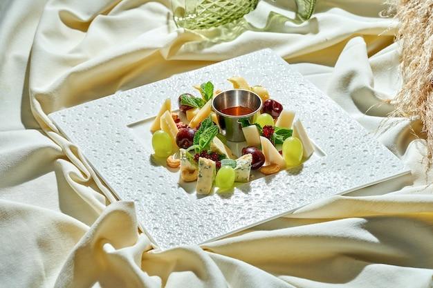 テーブルクロスの白いプレートに蜂蜜、ブドウ、ナッツを入れたさまざまなチーズの盛り合わせ。おやつ