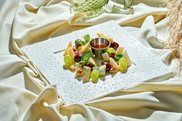 Assorted different cheeses with honey, grapes and nuts in a white plate on a tablecloth. snacks