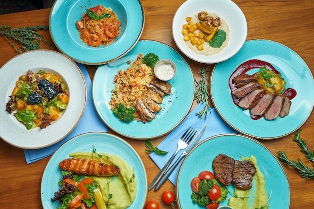 木製のテーブルのさまざまな料理の盛り合わせ。アヒルの胸肉、クスクス、チキン、ステーキ、サーモンのグリル、サラダ付きのダイニングテーブル。トップビュー、食品フラットレイアウト
