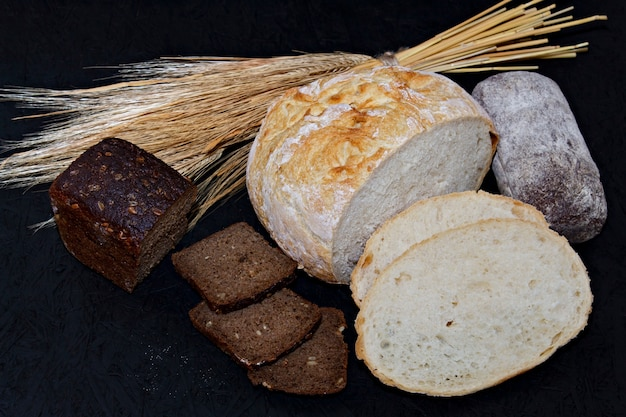 Assorted different kinds of white and black bread on a black background.