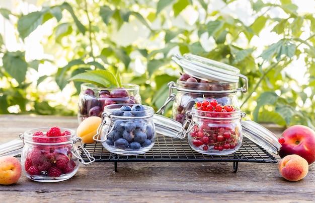 Ассорти из разных летних ягод в стеклянных банках на садовом столе