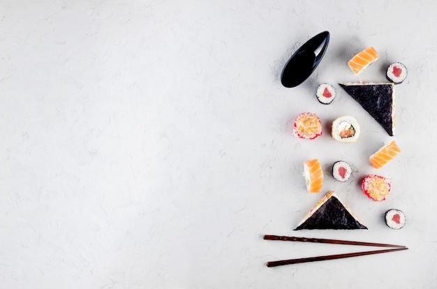 Ассорти разных суши и роллов с соевым соусом, имбирем, васаби и палочками для еды