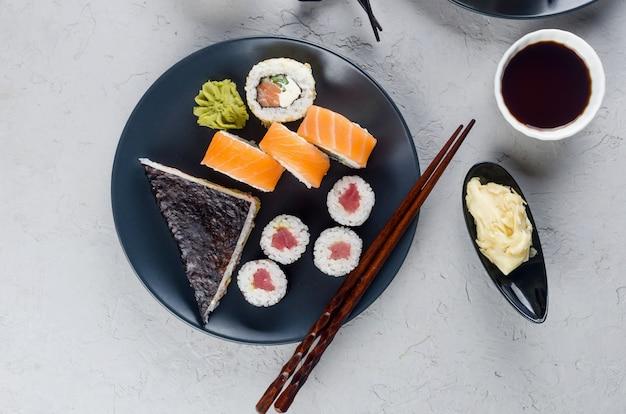Ассорти из разных суши-роллов на тарелке и соевый соус, имбирь, васаби и палочки для еды