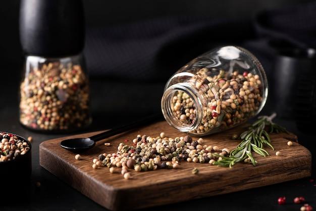 Ассорти различных видов душистого перца в стеклянной банке на деревянной доске, крупный план