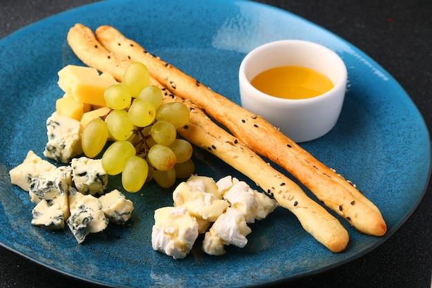 Ассорти из различных видов сыра с виноградом, медом и хлебом крупным планом