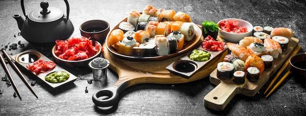 さまざまな種類の日本の寿司とロールの盛り合わせ。暗い素朴なテーブルの上