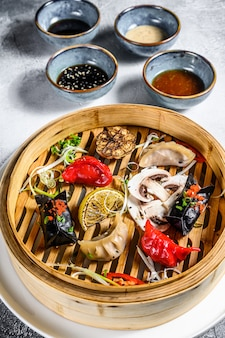 蒸し器での点心の盛り合わせ。中華料理のセットです。灰色の背景。上面図